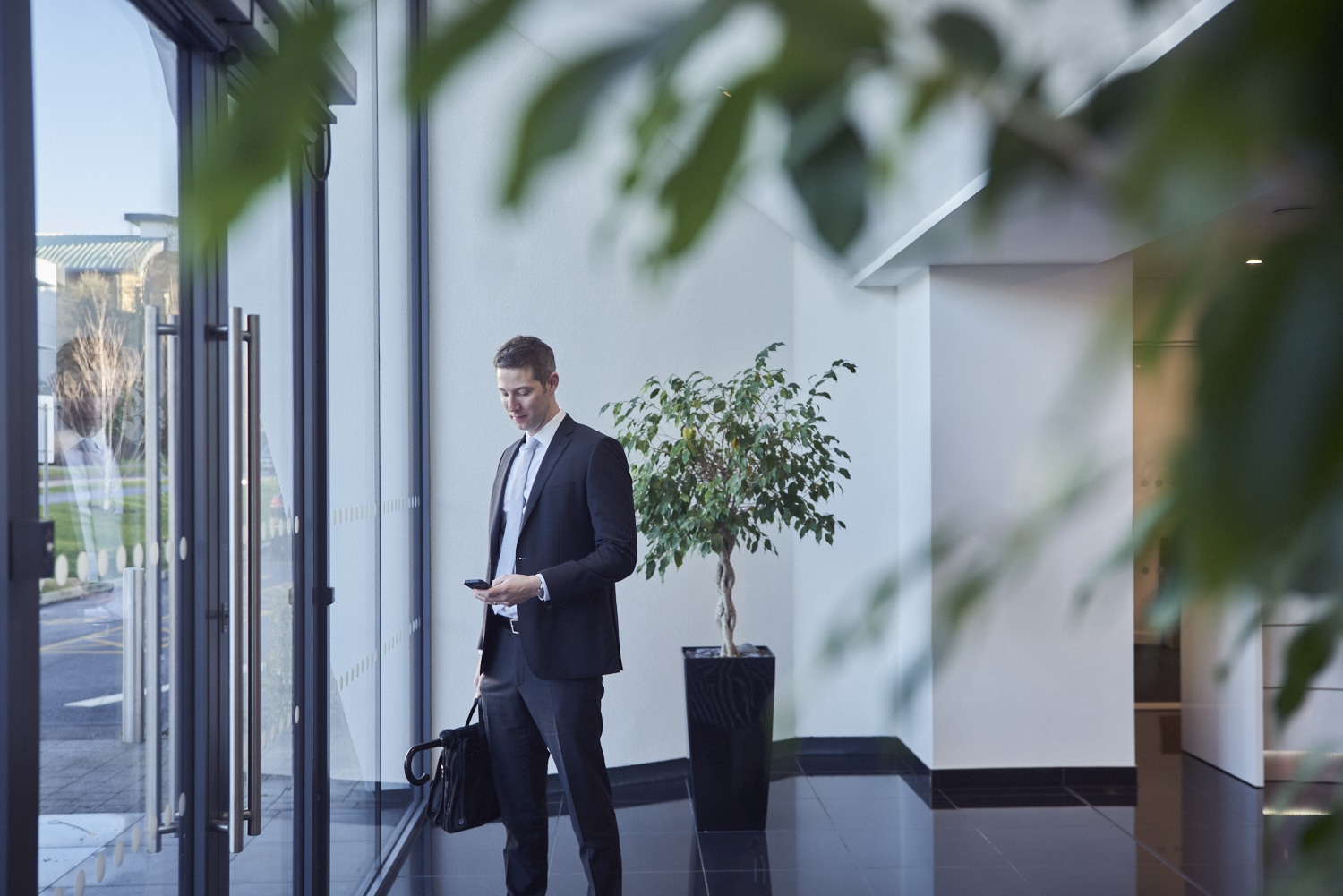 Man in a suit standing in an office reception using his phone